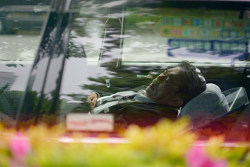 tokyo taxi driver sleeping leaned back in the driver seat