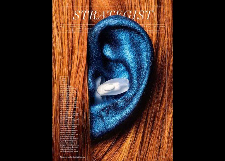 Strategist magazine cover showing a blue ear with Happy ears earplug inside the ear