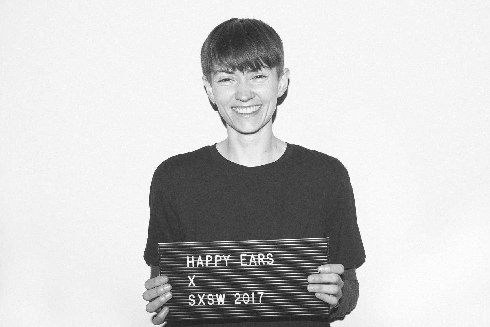 smiling woman with short hair holding up Happy Ears sign